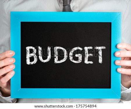 Budget. Business woman holding board on the background with business word  - stock photo