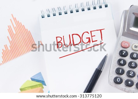 Budget concept - Financial accounting stock market graphs analysis. Calculator, notebook with blank sheet of paper, pen on chart. Top view - stock photo
