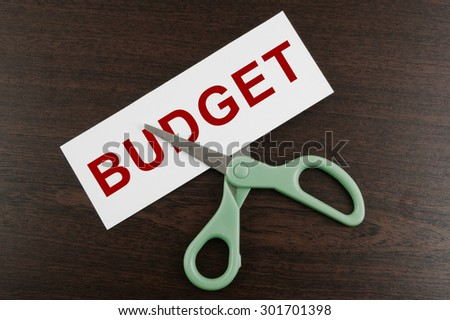 Budget cut business concept, scissors cutting paper with word budget - stock photo
