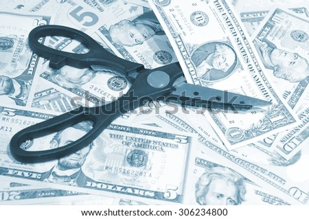 Budget cut concept with scissors and American dollars  - stock photo