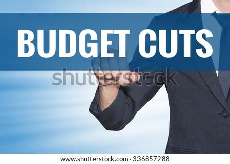 Budget Cuts word Business man touching on blue virtual screen - stock photo