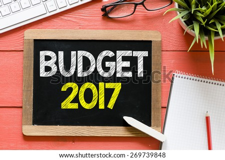 Budget 2017 Handwritten on blackboard. Budget 2017 Handwritten with chalk on blackboard, keyboard,notebook,glasses and green plant on wooden background - stock photo