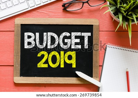 Budget 2019 Handwritten on blackboard. Budget 2019 Handwritten with chalk on blackboard, keyboard,notebook,glasses and green plant on wooden background - stock photo