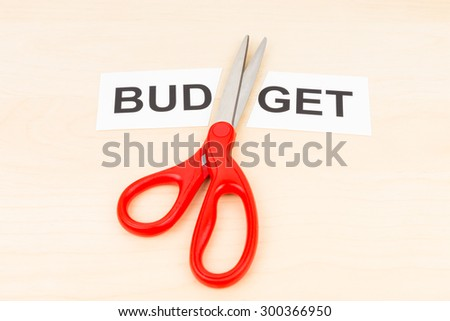 Budget in paper cut by scissor on wooden desk concept budget cut - stock photo