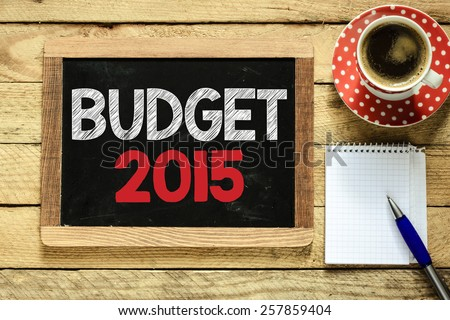 Budget 2015 sign on blackboard. Budget 2015 sign on blackboard with cup of coffee, notebook and pen on wooden background - stock photo