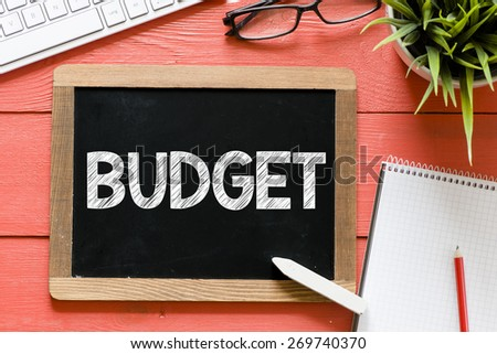 Budget word Handwritten on blackboard. Budget word Handwritten with chalk on blackboard, keyboard,notebook,glasses and green plant on wooden background - stock photo
