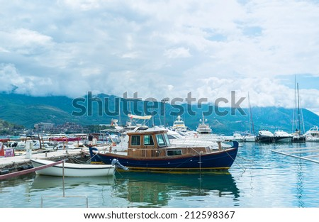 BUDVA, MONTENEGRO - JULY 12, 2014: The shipyard with the old fishing boats, tiny tourist boats and luxury yachts surrounded by mountains covered with the heavy clouds, on July 12 in Budva