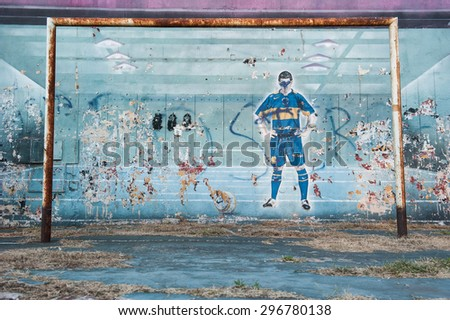BUENOS AIRES, ARGENTINA, FEBRUARY 15: Damaged graffiti in popular area of Boca shows football player ready to shoot at the ball on February 15, 2011 Buenos Aires. - stock photo