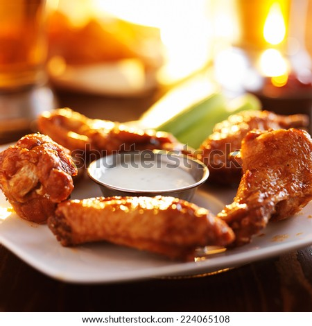 buffalo barbecue hot chicken wings around ranch sauce with celery - stock photo