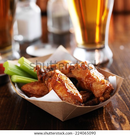buffalo chicken wings in disposable tray with celery and ranch - stock photo