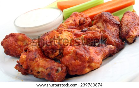 Buffalo chicken wings with celery, carrots, and blue cheese dipping sauce. - stock photo