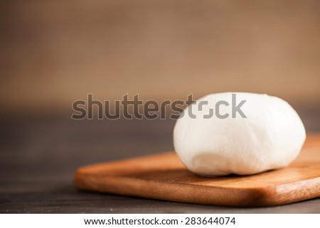 Buffalo mozzarella. Cutting board. Wooden table. Selective focus. - stock photo