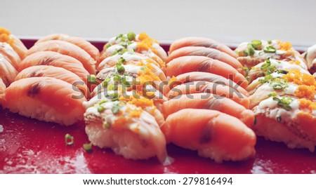 Buffet catering style Sushi Set in restaurant - salmon and crab sticks Maki Sushi and Nigiri Sushi, retro filter effect  - stock photo