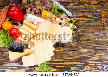 Buffet display with a selection of different cheeses displayed on a wooden cheeseboard garnished with cocktail onions, olives, blackberries, grapes, tomato and peppers, overhead view with copyspace