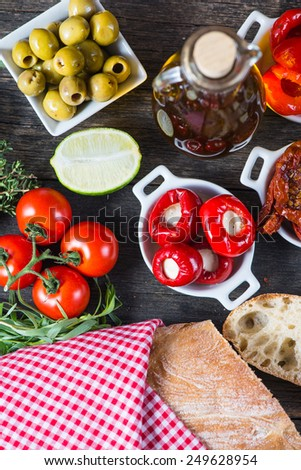 Buffet style authentic spanish tapas on table with fresh herbs - stock photo