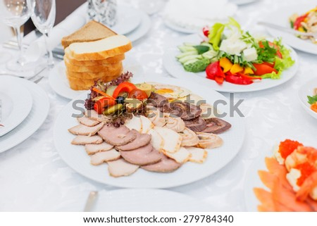 Buffet table served with tasty meals. Assorted meat, stuffed chicken roll, ham with mushrooms and greens decorated - stock photo