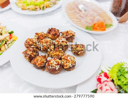 Buffet table served with tasty meals. Stuffed mushrooms with cheese, meat and vegetables - stock photo