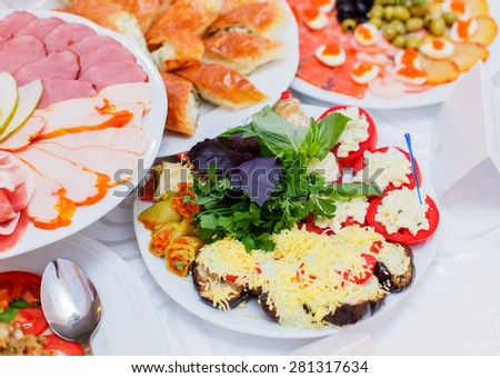 Buffet table served with tasty meals. Stuffed vegetables and cream cheese decorated with greens - stock photo