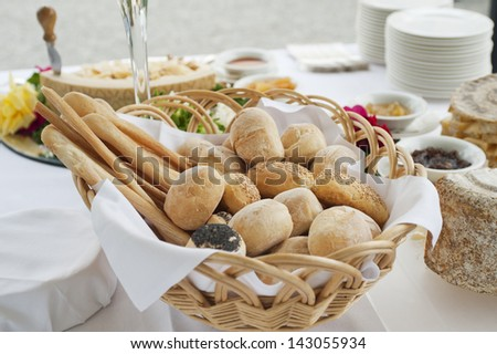 buffet table with basket of bread in foreground - stock photo