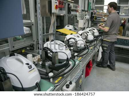 "BUHLERTAL, GERMANY - MARCH 30, 2014:  Machine-building plant of the company Karcher ""Alfred Karcher GmbH & Co. KG"".  Unidentified worker collects high-pressure apparatus."