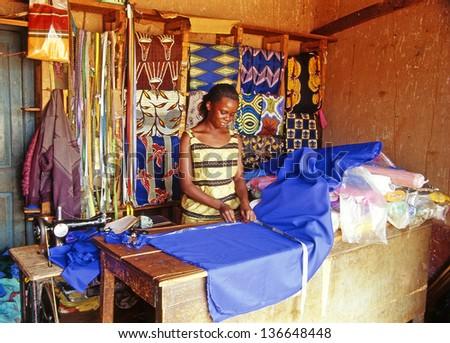 BUIKWE REGION, AJIJJA, UGANDA - JULY 26: An unidentified village dressmaker in her shop on July 26, 2004 in village Ajijja, Uganda. Typical colored dresses are the pride of the local women. - stock photo