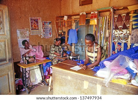BUIKWE REGION, AJIJJA, UGANDA - JULY 26: An unidentified village dressmakers in her shop on July 26, 2004 in village Ajijja, Uganda. Typical colored dresses are the pride of the local women. - stock photo