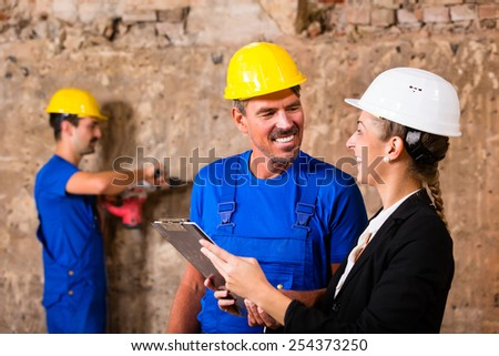 Builder and supervisor on construction site discussing over plans - stock photo
