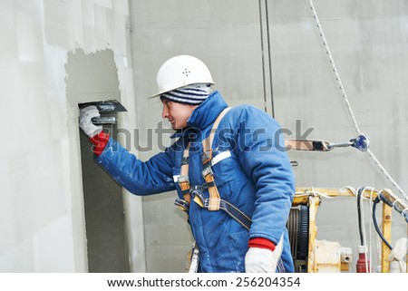 builder at facade plastering work during industrial building with putty knife float - stock photo