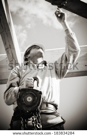 builder at work with winch on roof construction.Monochrome - stock photo
