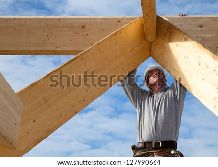 builder at work with wooden  roof construction - stock photo