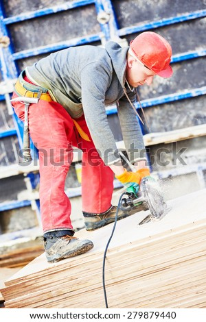 builder carpenter worker with disk saw cutting plywood for falsework construction before concreting at building site - stock photo