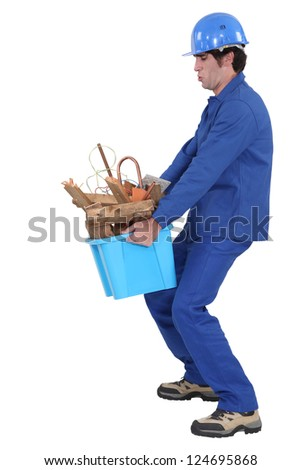 Builder carrying box of waste - stock photo