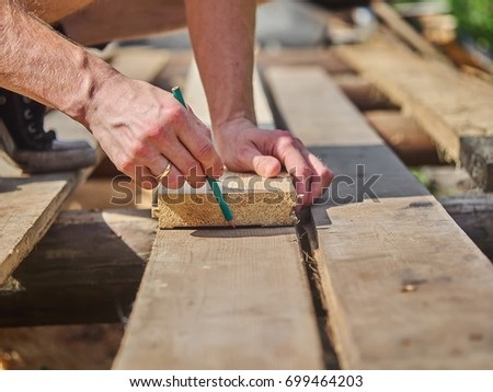 Builder drawing on a wooden board