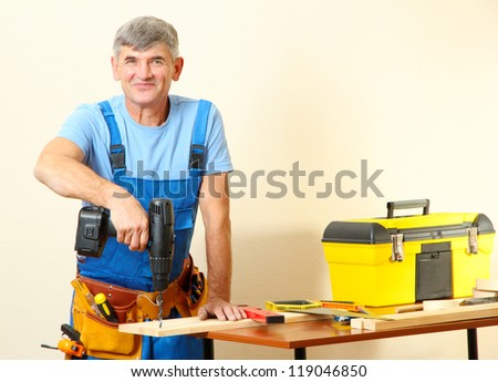 Builder drills board on table on wall background - stock photo
