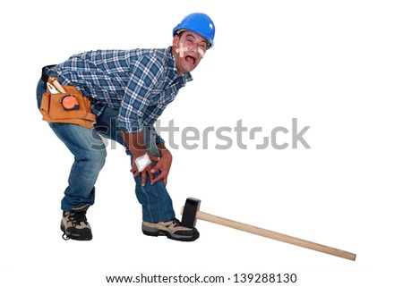 Builder dropping hammer on foot - stock photo