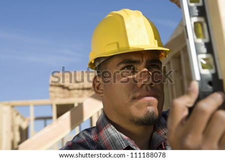 Builder examining framework at construction site - stock photo