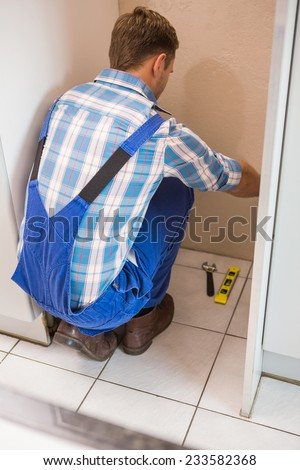 Builder fixing tiles on the floor of a new home