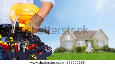 Builder handyman with construction tools. House renovation background. - stock photo