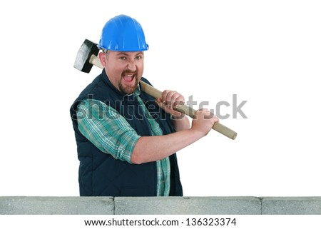 Builder hitting a wall with a sledgehammer - stock photo