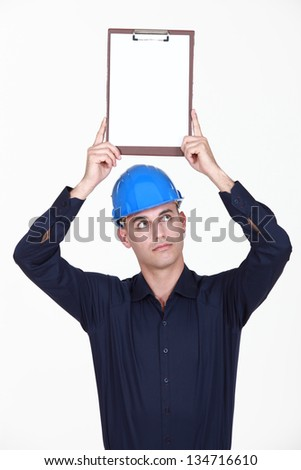 Builder holding clipboard over head - stock photo