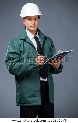 builder in a green jacket and a white helmet writes in a notebook - stock photo