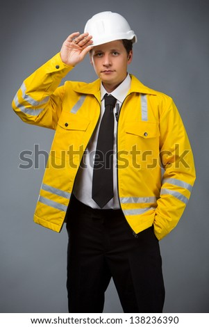 builder in a yellow jacket holding his hand to his helmet - stock photo