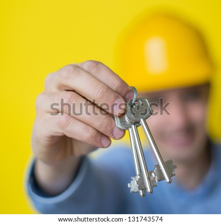 Builder in helmet hands keys to a new apartment - stock photo