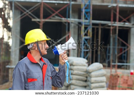Builder in helmet with a megaphone