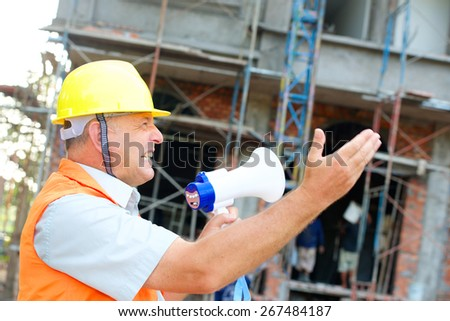 Builder in helmet with a megaphone vertical photo