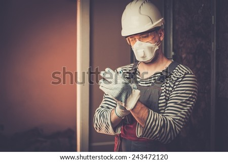 Builder in protective wear during new building construction  - stock photo
