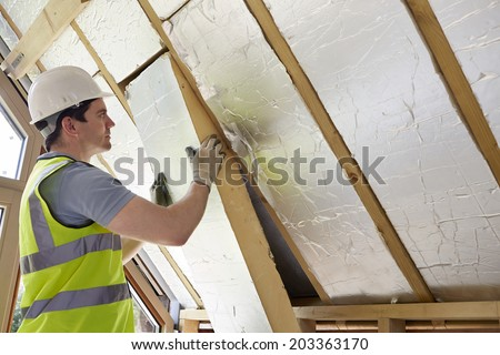Builder Installing Insulating Board Into Roof Of House - stock photo