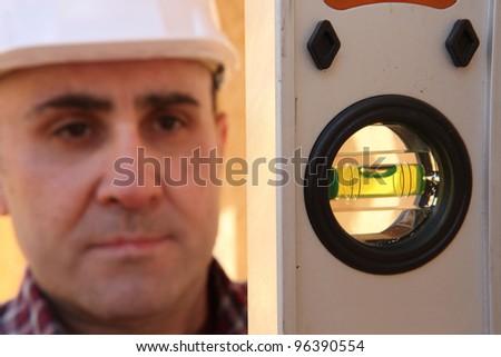Builder knelt holding spirit level - stock photo