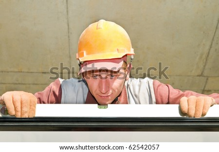 Builder laborer in work wear and hard hat at construction site with level tool - stock photo