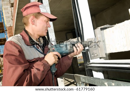 Builder laborer in work wear making a hole with drilling machine